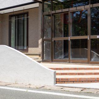 お庭正面。やわらかいカーブをつけた白壁とライトブラウンの階段アプローチでやさしい印象の正面に。