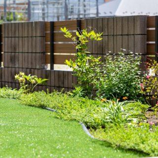 人工芝と草花を植えた花壇スペースは高低差がなく、境目を感じずフラットな印象に。