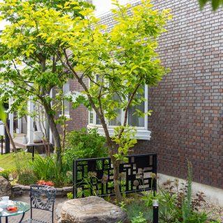 既存であった木のまわりには大きな庭石とデザインフェンス、花壇をバランス良く配置しています。