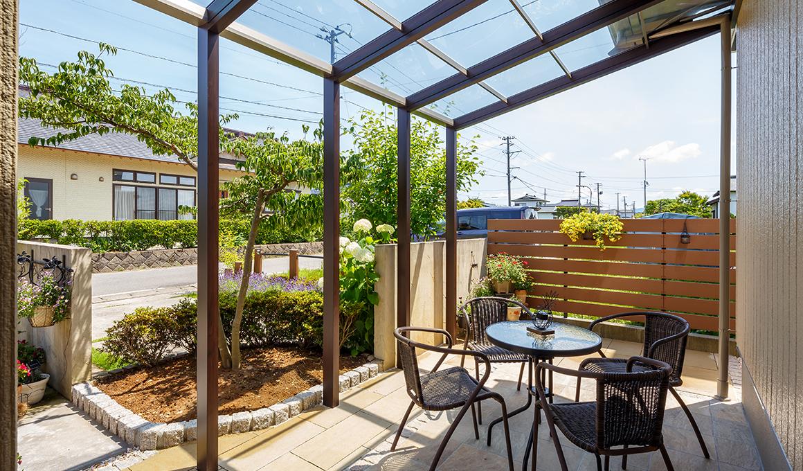 屋根で日差しが出来るテーブルセットのあるお庭